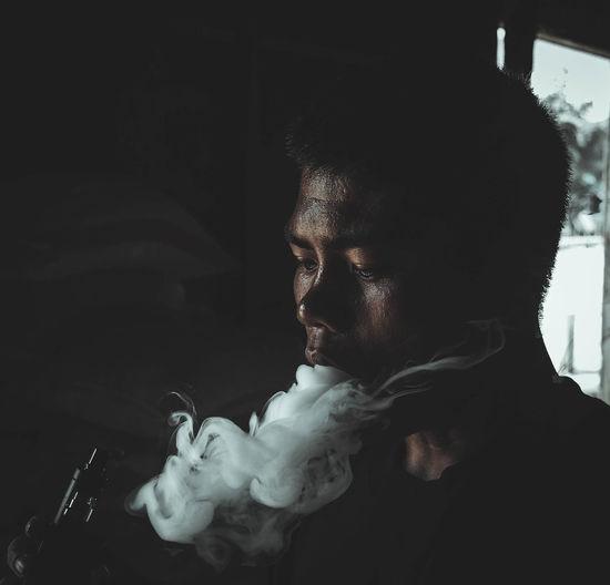 Close-up of man smoking electric cigarette