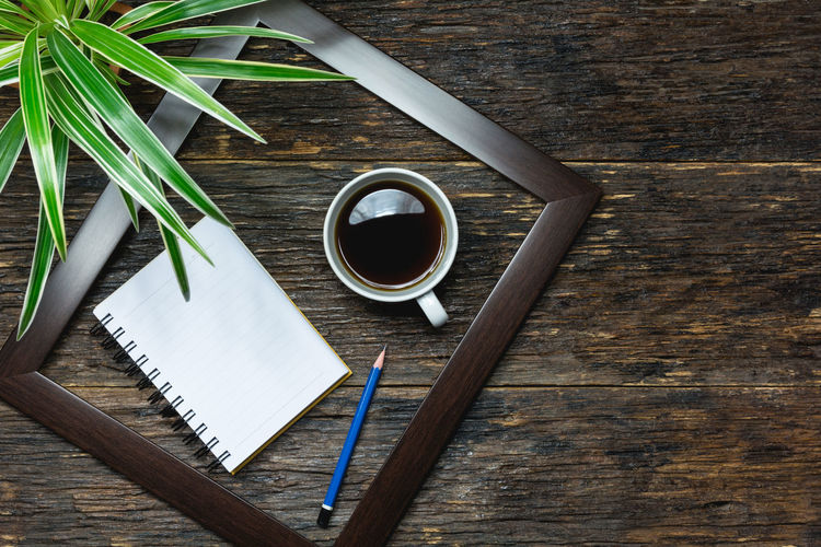 High angle view of coffee with plant by note pad and pencil on wooden table