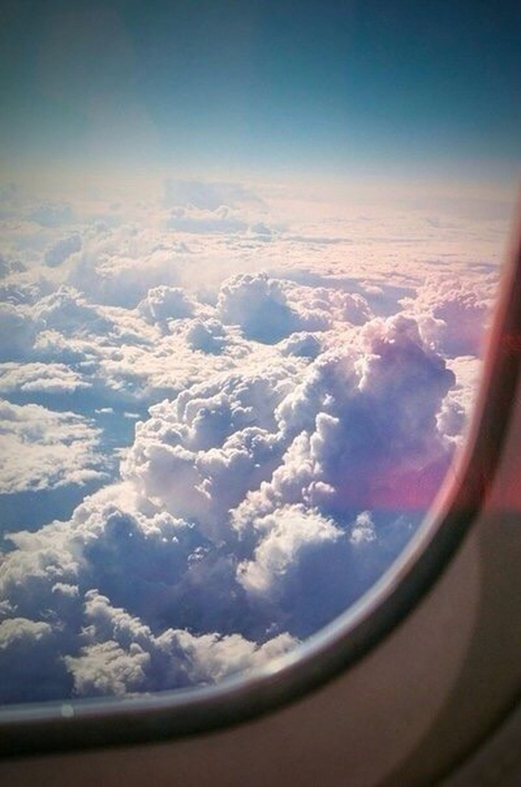 transportation, airplane, mode of transport, vehicle interior, sky, window, air vehicle, part of, transparent, glass - material, cropped, cloud - sky, flying, aircraft wing, scenics, travel, cloudscape, cloud, beauty in nature, aerial view