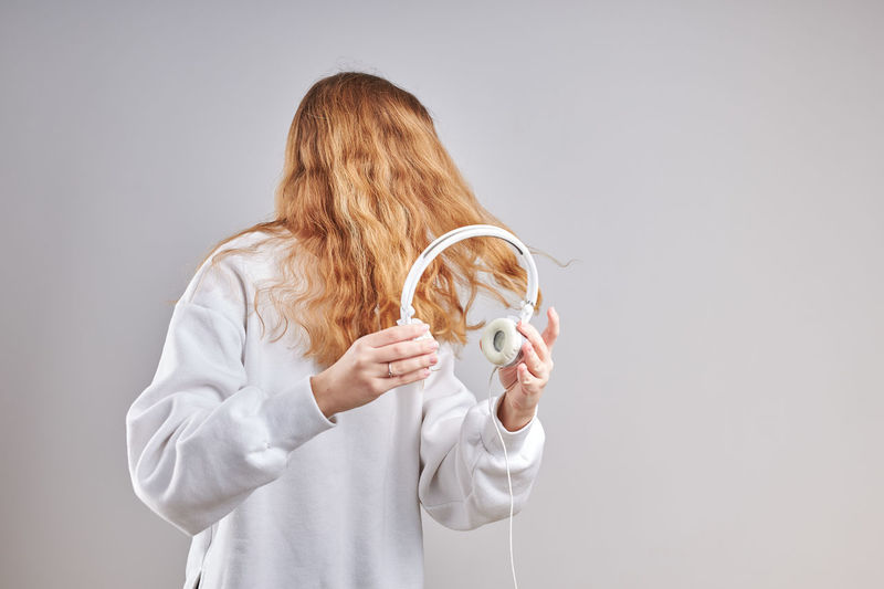 Young woman holding headphones while standing against gray background
