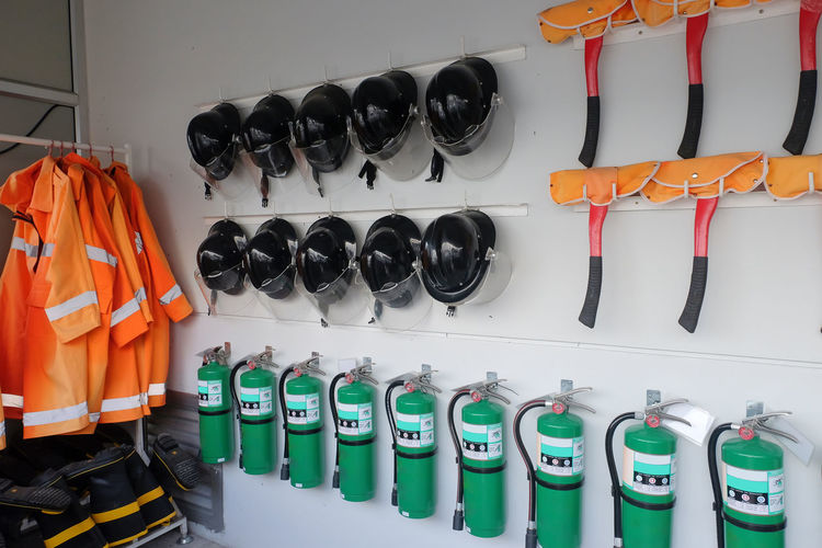 Fire extinguishers with helmets hanging on wall