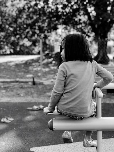 Childhood Park - Man Made Space Rear View Girls One Person Playing Leisure Activity Playground Real People Casual Clothing Outdoors Day Child Focus On Foreground Tree Sitting Full Length Nature Children Only People EyeEmNewHere EyeEmNewHere Black And White Friday