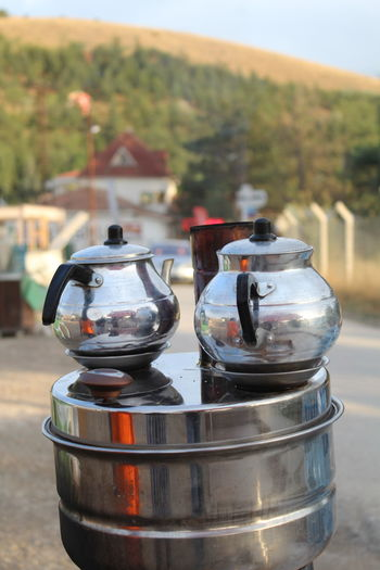 Close-Up Of Kettles On Container Against Mountain
