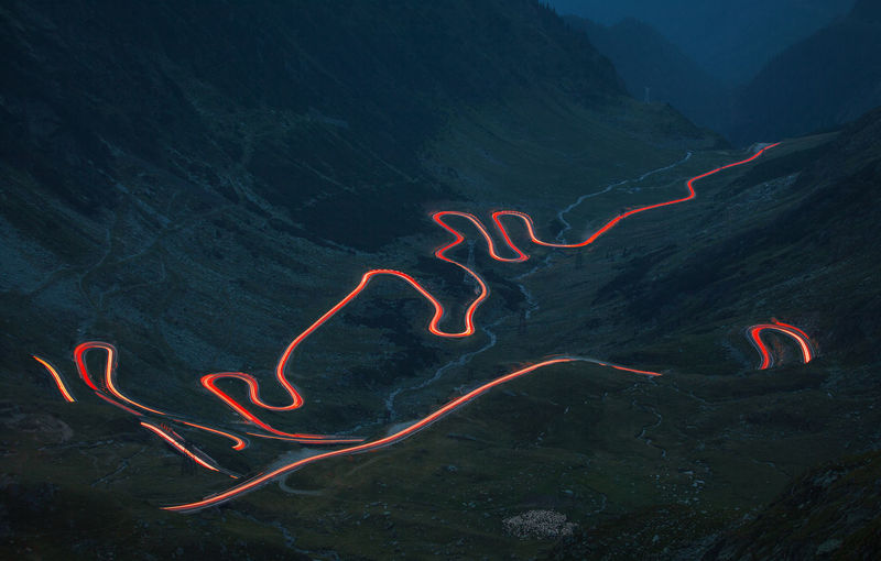 Transfagarasan road from Fagaras Mountains after sunset. Curves Dark Lights Pass Red Road Shape Traffic Transfagaraşan Transportation Curve High Angle View Illuminated Landscape Long Motion Mountain Night No People Speed Street Trail Valley View From Above Winding Road Fresh on Market 2017 EyeEm Ready   Humanity Meets Technology