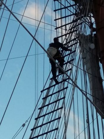 Young Adult Cable Adult Sky Steel Cable Manual Worker Rappelling Navy Ship Vertical EyeEm Best Shots Sailing EyeEm Gallery Nautical Vessel Nautical Equipment Tied Personal Perspective Nautical Theme Mode Of Transport High Section Mast Ship Mast Connection Dramatic Sky Silhouette Skyscraper