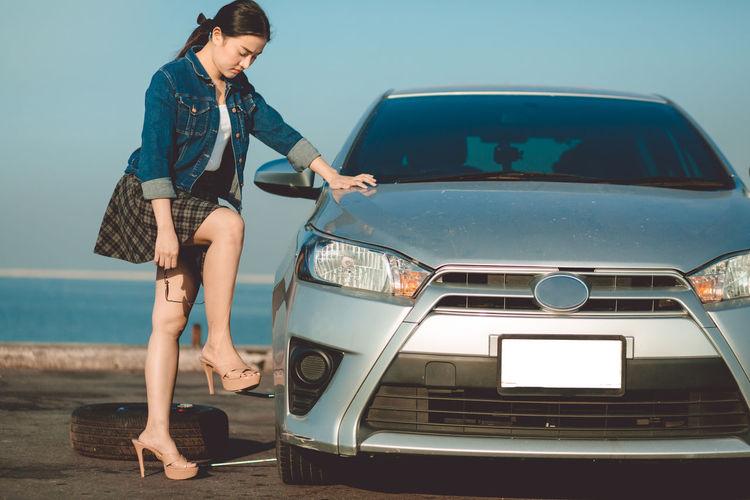 Full length of woman standing on car against sky