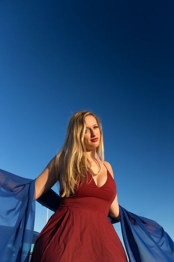 Low Angle Portrait Of Young Woman Standing Against Clear Blue Sky