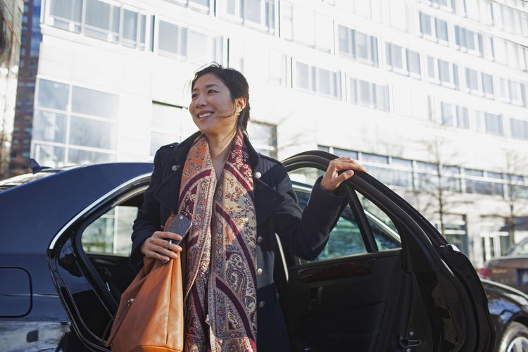 Mid adult woman standing against car in city
