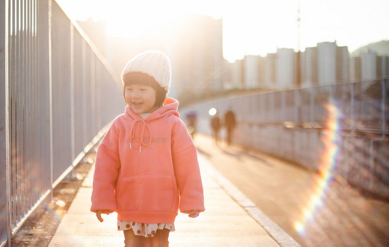 Full length of cute boy on footpath in city