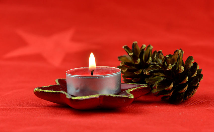 Close-up of tea light candles on red table