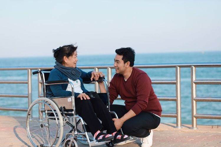 Senior woman with grandson sitting on wheelchair by sea