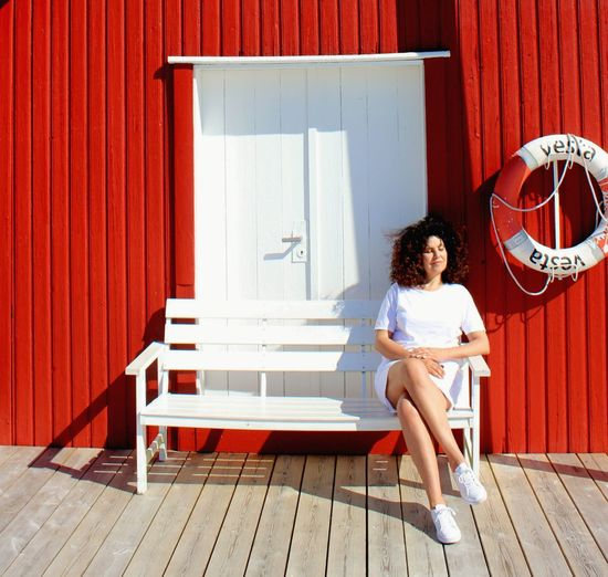 Woman Sitting On Bench Against Red Wall