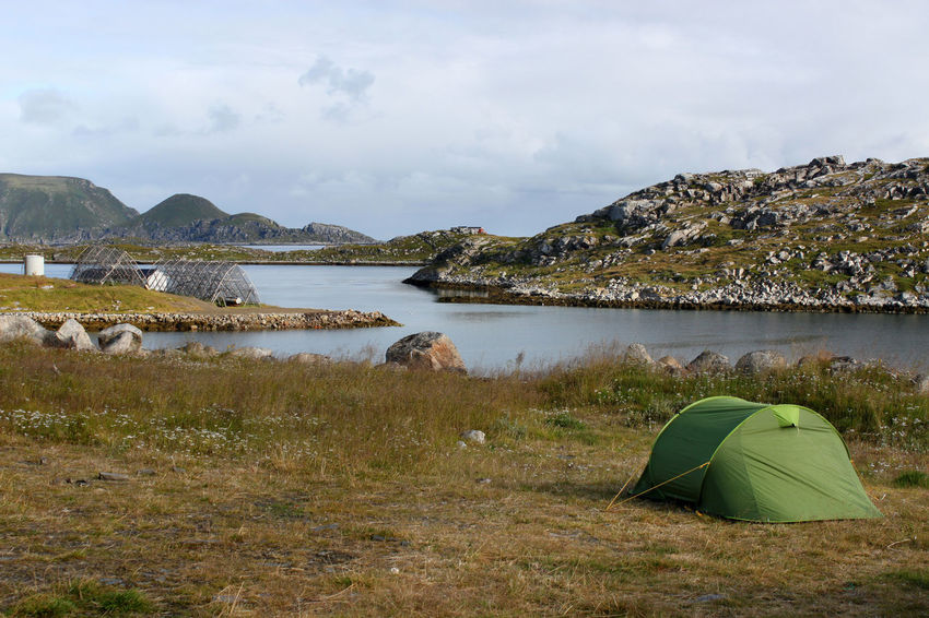 Camping in a tent on a meadow next to a bay with a little island and Gjesvaer with Storstappen near Nordkapp, Norway Adventure Atlantic Ocean Backcountry Bay Camping Coast Coastline Factory Gjesvaer Harbor Houses Islands Lake Meadow Mountain Nordkapp North Cape Norway Outdoors Scenics Shed Shore Stockfish Storstappen Village
