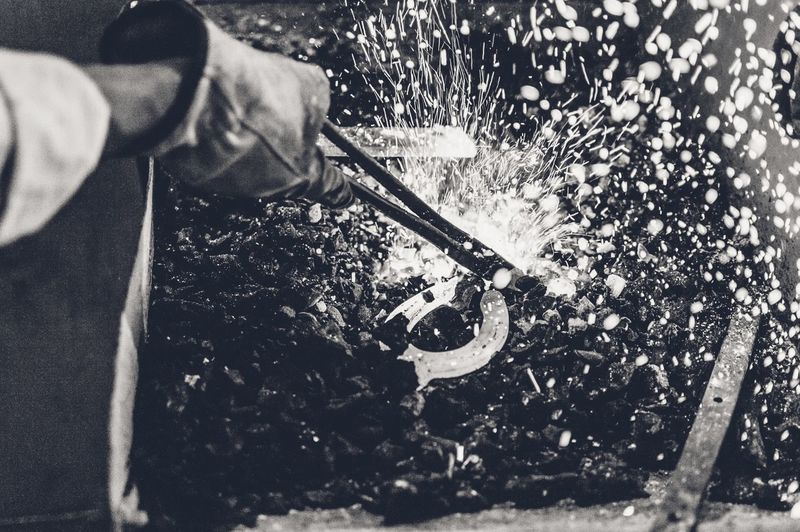 Cropped Image Of Blacksmith Heating Metal Over Coal In Workshop