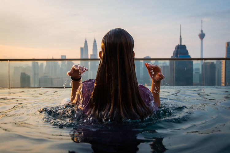Rear view of woman in infinity pool against buildings in city