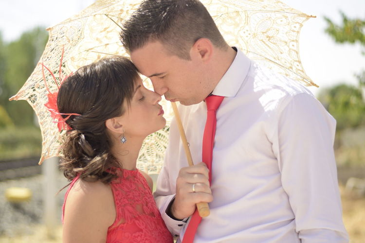Young couple rubbing noses while holding umbrella on sunny day