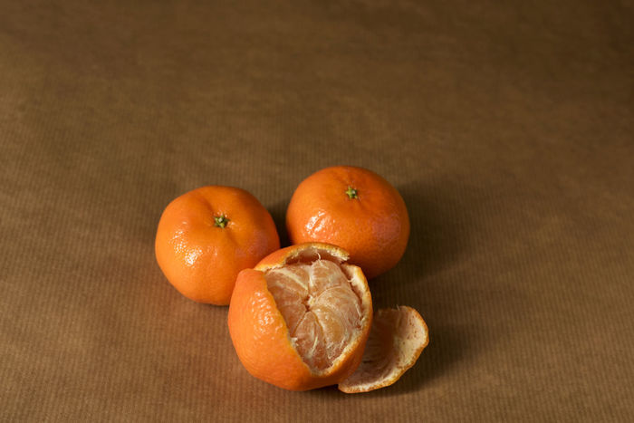 Three clementines on brown paper, with one half-peeled Citrus  Freshness Minimalist Brown Brown Paper Citrus Fruit Clementine Clementines Foodphotography Fruit Healthy Healthy Eating Healthy Food Ingredient Mandarins Minimal Minimalism Monochromatic Monochrome Mood Obst Orange Color Peel Peeling Pile Still Life