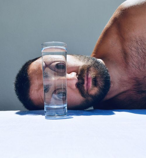 Close-up of man drinking glass on table