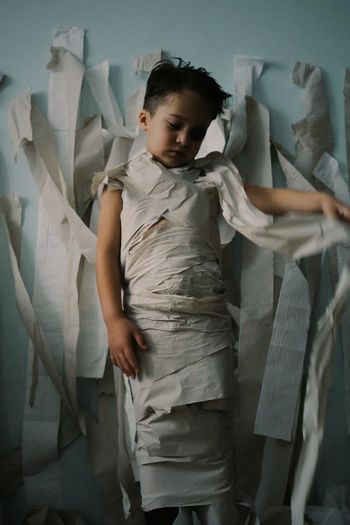 Boy wrapped in toilet paper standing at home