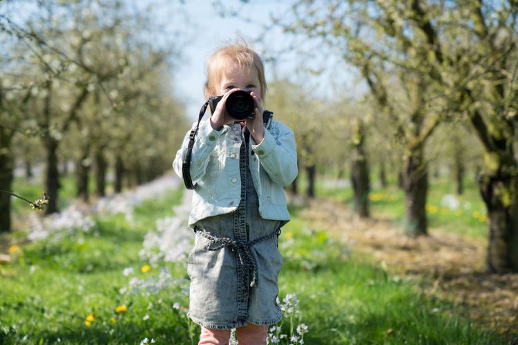 My little protege Beautiful Camera Casual Clothing Child Childhood Cute Girl Holding Holding Camera Leisure Activity Nature One Person Outdoors Photography Sweet Trees Press For Progress Stay Out