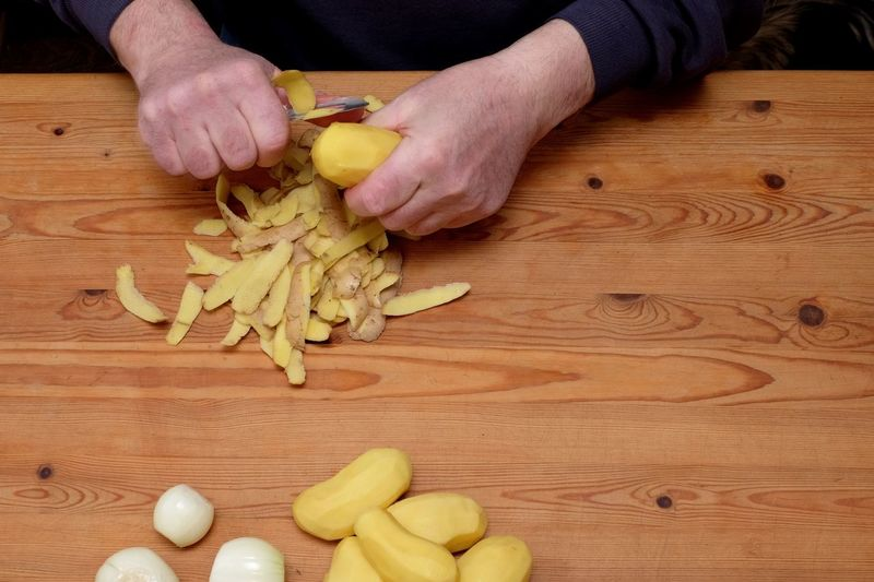 Cropped hands of man peeling potatoes on table