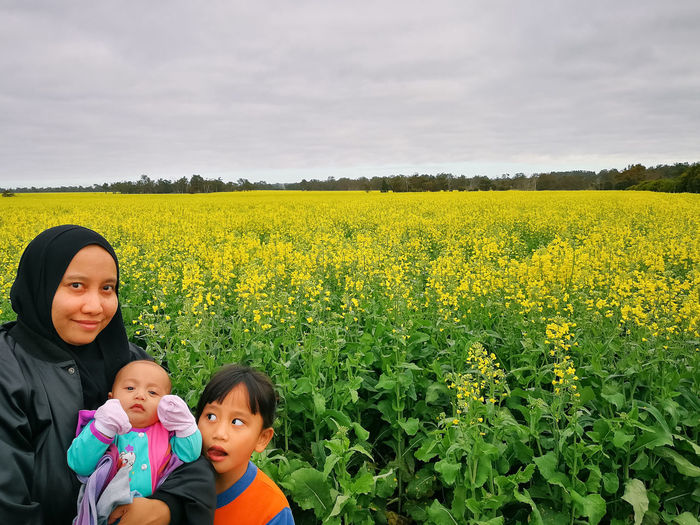 View over a blossoming rapeseed field in a rural landscape. Yellow Color Yellow Flower Yellow Fields Rapeseed Field Rapeseed Nature Land Plant Child Childhood Real People Yellow Beauty In Nature Portrait Togetherness Field Sky Females Family Bonding Flower Lifestyles Positive Emotion Innocence Yellow Flowers