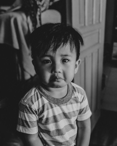 Sad baby with real emotion in a dark mood black and white photo.