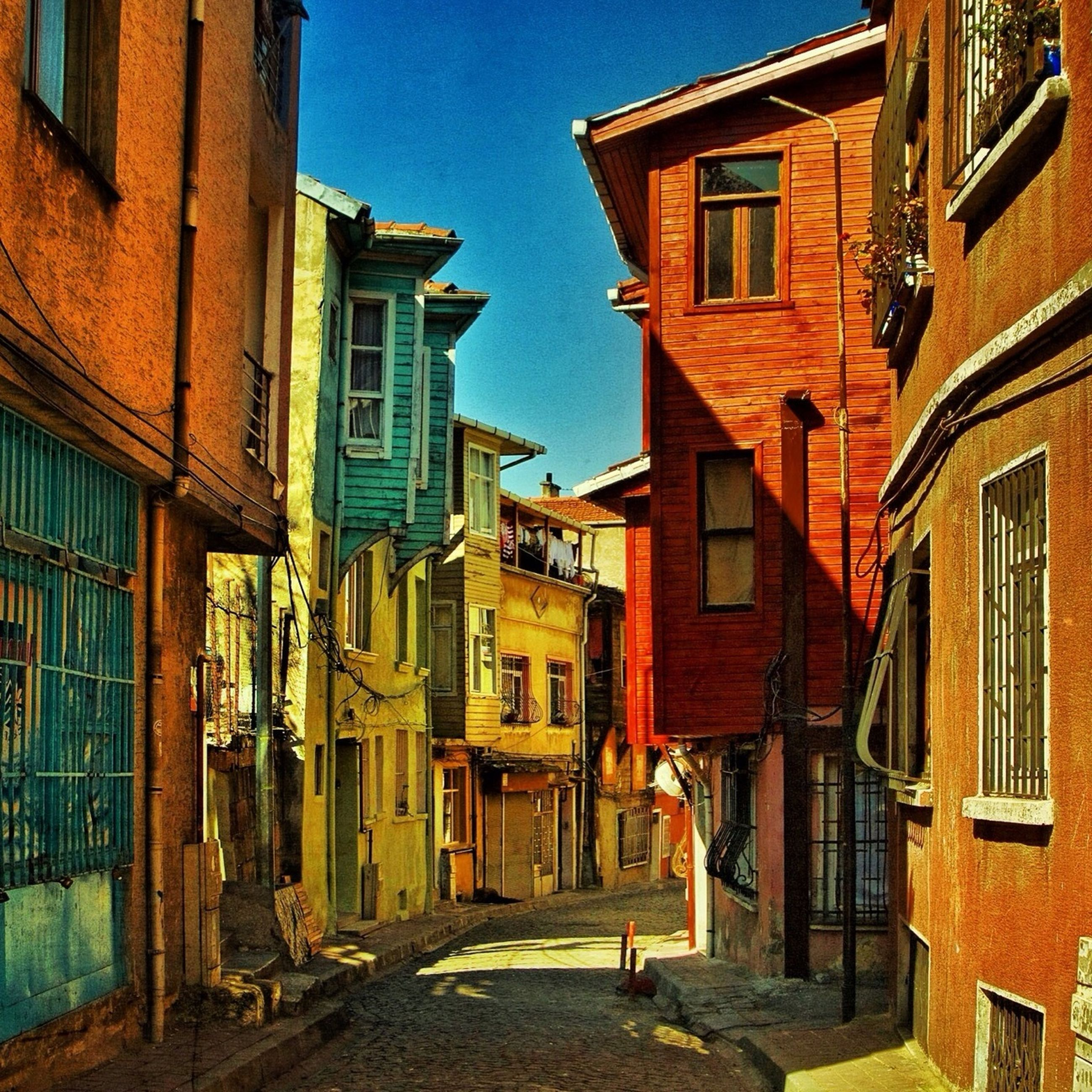 building exterior, architecture, built structure, residential building, residential structure, city, building, window, house, street, sunlight, shadow, blue, residential district, city life, clear sky, outdoors, day, alley