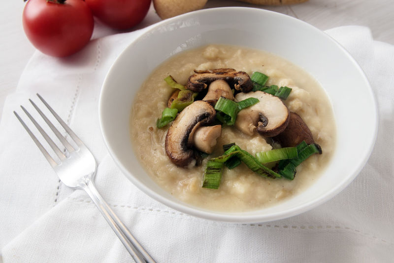 Parsnip puree with roasted mushrooms and leek in a bowl on a white tablecloth, healthy eating and slimming diet from organic vegetables Cooking Diet Leek Puree Vegetarian Food Bowl Champions Day Food Food And Drink Fork Freshness Healthy Eating Low Carb Mash Mashrooms Napkin No People Parsnip Ready-to-eat Serving Size Vegetable White