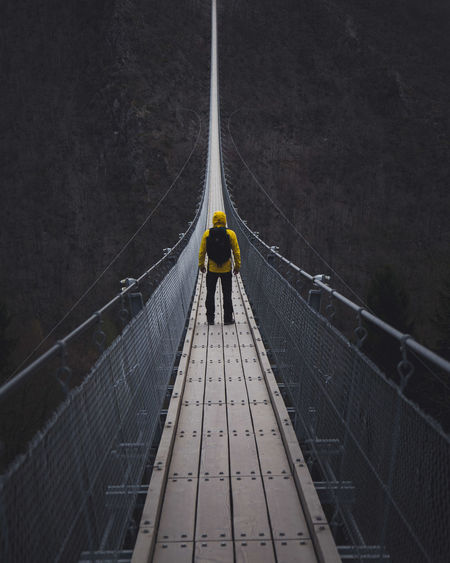 Man standing on footbridge