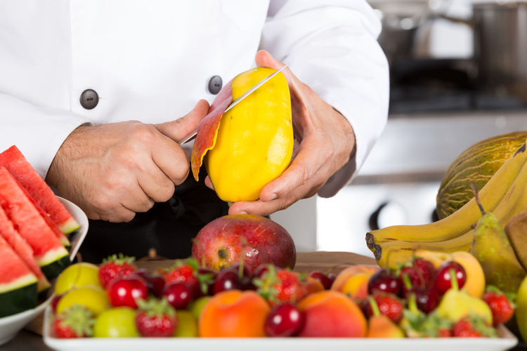 Midsection of chef cutting fruits in commercial kitchen