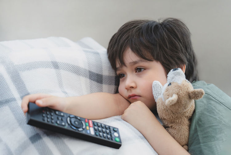 Cute boy holding remote controller at home