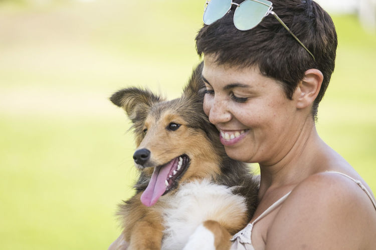 Close-up of smiling woman carrying dog