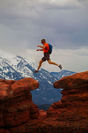 Full length of man jumping on rock against sky