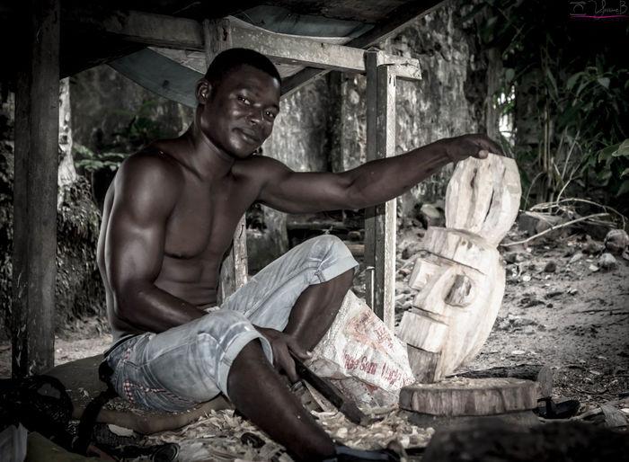 Portrait of mid adult man carving wood at workshop