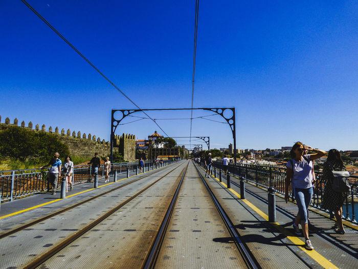 People walking on railroad tracks against clear blue sky
