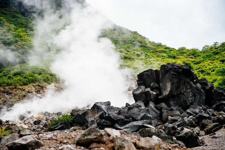 Smoke coming from crater by rocks at hakone