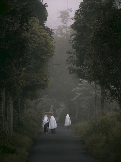 Rear view of people wearing traditional clothing walking on road