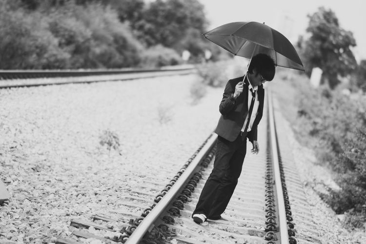 Businessman with umbrella walking on railroad track