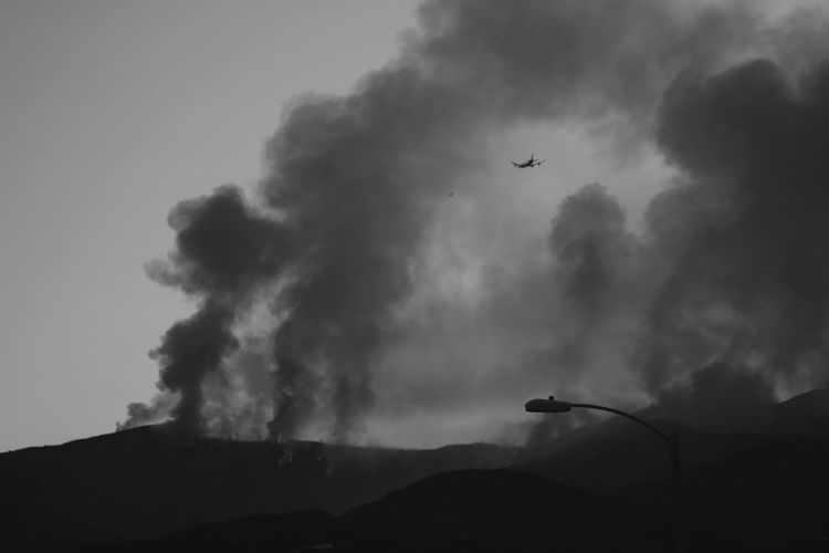 Low angle view of silhouette airplane flying in wildfire