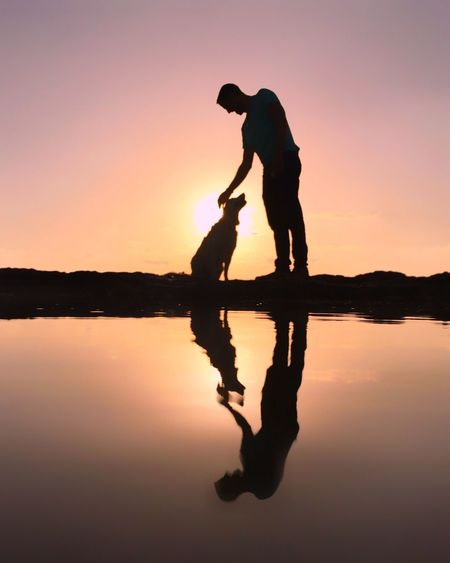 Silhouette father with son against sky during sunset