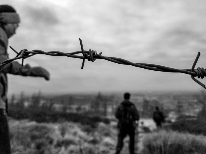 Close-up of barbed wire fence on field against sky