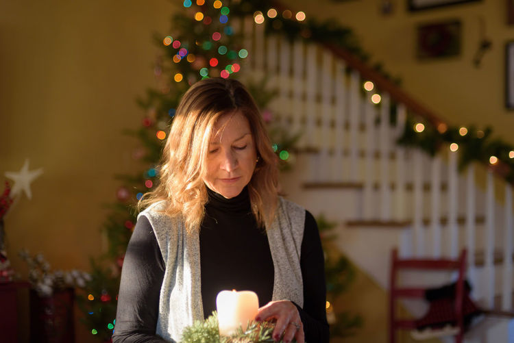 Mature woman holding illuminated candle at home during christmas
