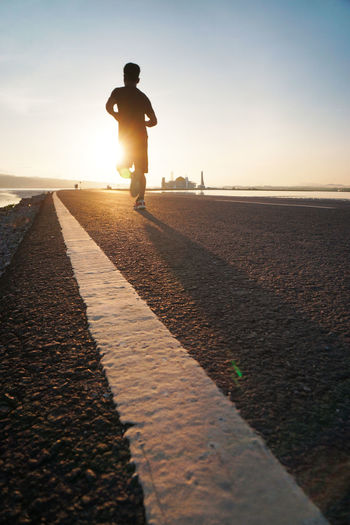 Rear view full length of boy jogging on road during sunrise