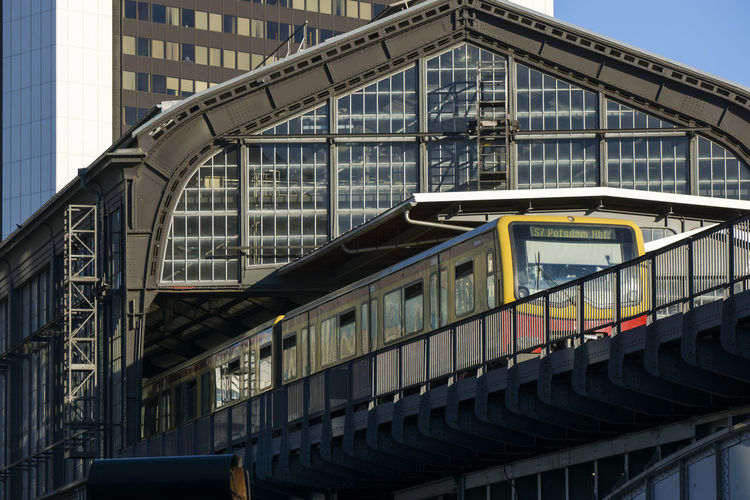 Low angle view of s-bahn train on bridge against buildings