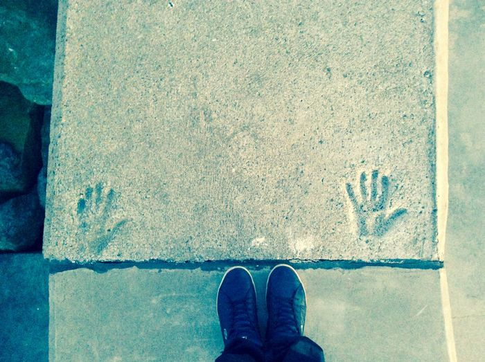 Low section of man standing by handprint on pathway