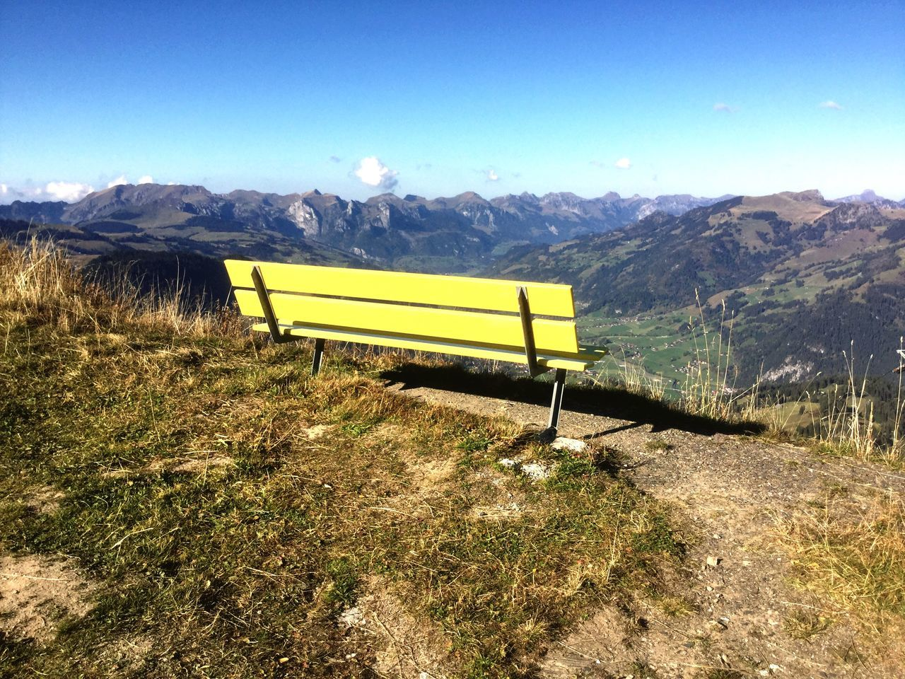 Empty Bench On Field In Front Of Mountain Against Sky