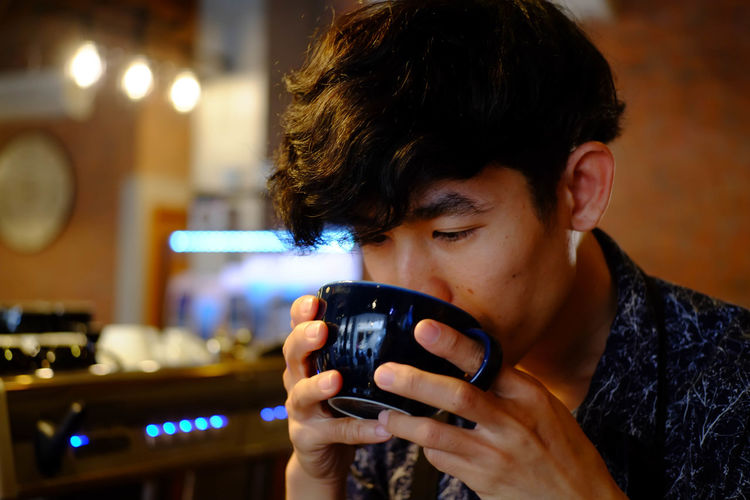 Close-Up Of Man Drinking Coffee At Cafe
