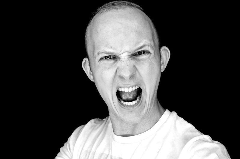 Close-Up Portrait Of Man Screaming Against Black Background