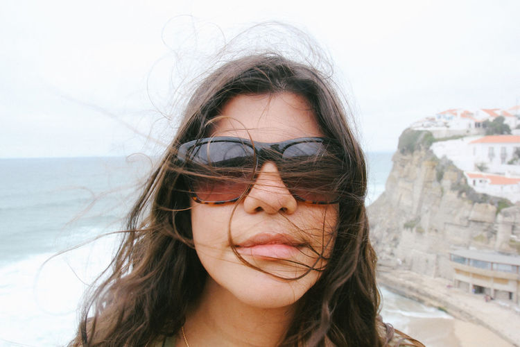 Close-up portrait of young woman wearing sunglasses against beach